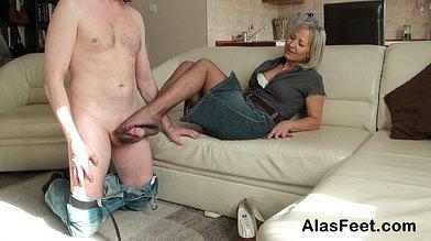 Elegant mature woman in a denim skirt gives a foot job