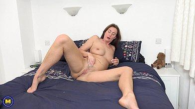 Gorgeous British milf Lara Latex masturbates on a bed